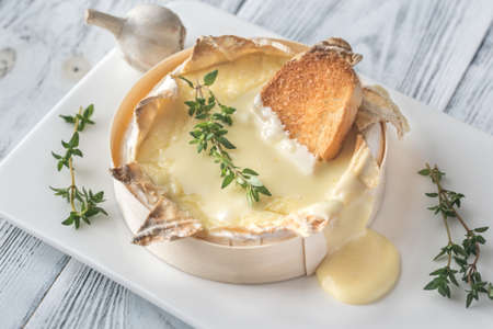 Photo pour Baked Camembert cheese with toasted bread slices - image libre de droit