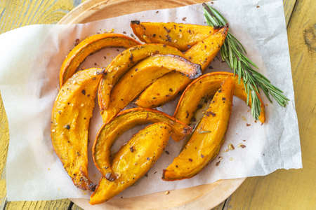 Photo pour Baked slices of pumpkin with seasonings and rosemary - image libre de droit