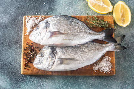 Photo pour Fresh dorada with thyme and halved lemon on the wooden board - image libre de droit