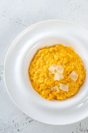 Photo for Portion of pumpkin risotto with slices of parmesan - Royalty Free Image