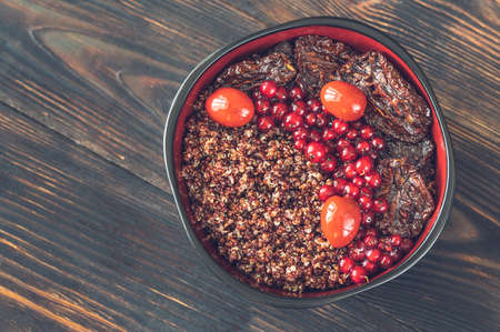 Photo pour Bowl of red quinoa with olives, sun-dried tomatoes, berries and nuts - image libre de droit