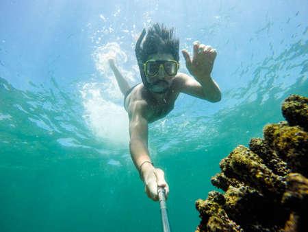 Photo pour Underwater selfie shot with selfie stick. Deep blue sea. Wide angle shot. - image libre de droit