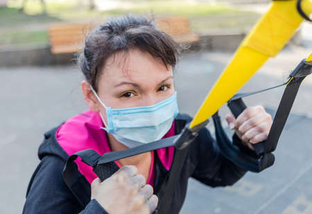 Asian young fitness sport woman training outside and wearing disposable medical mask. Dust and pollution and protection flu virus, influenza, coronavirus on city. Covid-19 person