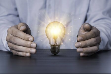 Photo for Two hands protecting the light bulb that is illuminating on the table. Creative protecting patents and ideas concept. - Royalty Free Image