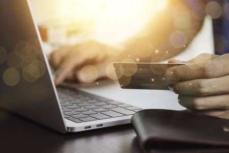 Foto de One hand holding credit card and another hand input order to computer laptop with shopping cart background. Online shopping and work from home concept. - Imagen libre de derechos