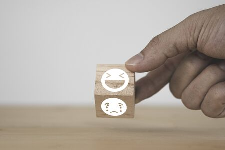 Photo pour Customer hand flipping happy  and smile face emotion which print screen on wooden block on sad emotion face. Customer service evaluation and copy space concept. - image libre de droit