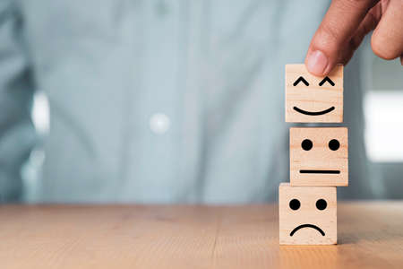 Photo pour Select emotion or mood concept , Hand holding smile face  or happy face which print screen on wooden cube block. - image libre de droit