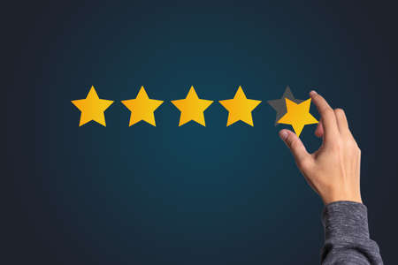Photo for Customer satisfaction and product service evaluation concept , Hand holding and put yellow star to five stars with copy space. - Royalty Free Image