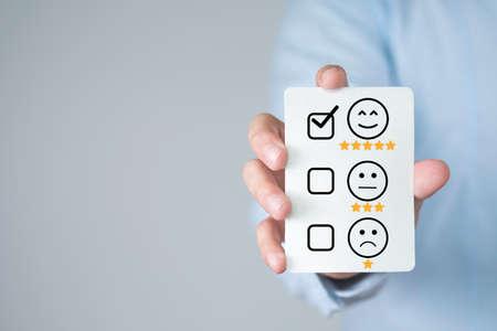 Photo pour Businessman holding product and service evaluation sheet. Customer satisfaction concept. - image libre de droit