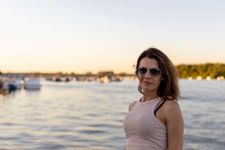 Foto de Beautiful woman wearing sunglasses at sunset by the river. Focus on the sunglasses - Imagen libre de derechos