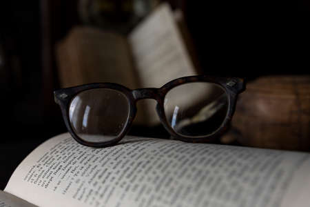 Foto de Old worn Glasses resting on an opened book with books and clock in background. Reading time concept - Imagen libre de derechos