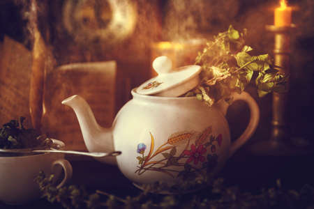 Photo pour Cup of Tea and Teapot on wooden table with vintage clock, burning candle and old book in the background - image libre de droit