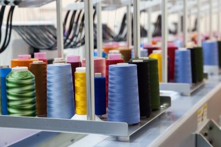 Photo pour Colorful reels of threads background - interior of industrial textile factory - image libre de droit