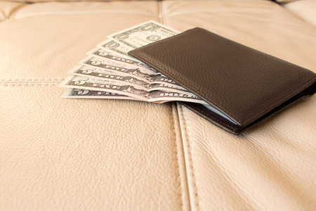 Brown leather wallet with dollars on the background of leather sofa
