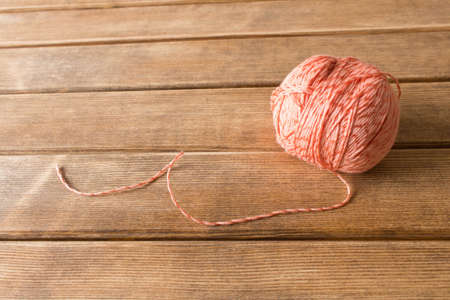 A ball of thread on the table . On the background of wooden table .