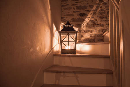 Photo for a large lantern with a burning candle on a wooden staircase and shadows and light aspects falling in all directions, in the background is a stone wall - Royalty Free Image