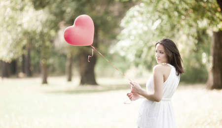 Sad Young Woman Standing with a Red Shaped Heart Balloon Outdoors
