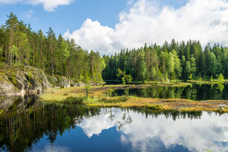 White summer clouds reflecting on the forest pond in Nuuksio National Park in Southern Finland