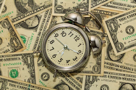 Photo for Alarm clock on carpet of dollar bills, time is money. - Royalty Free Image