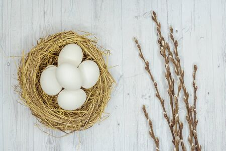 Photo for white Easter eggs in a nest and a willow on a gray wooden table. the view from the top - Royalty Free Image