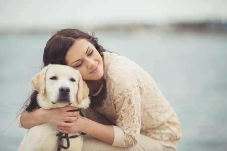 Portrait of beautiful young woman playing with dog on the sea shoreの写真素材