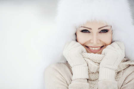 Beautiful winter portrait of young woman in the winter snowy sceneryの写真素材