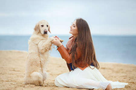 portrait of Beautiful woman with her dog on the beach near sea
