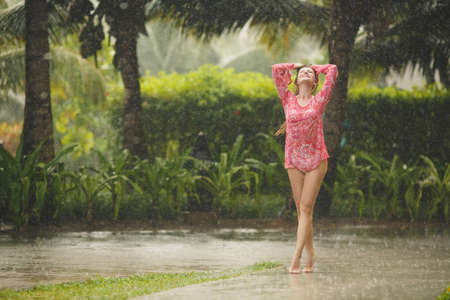 Portrait of a beautiful happy woman enjoying tropical rain falling on her in an exotic garden