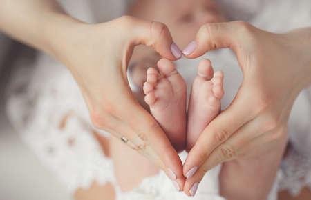 Newborn baby feet in mother hands.Masseur massaging little baby\'s foot, shallow focus. Newborn baby feet in mother\'s hands.Mother making massage of child\'s foot