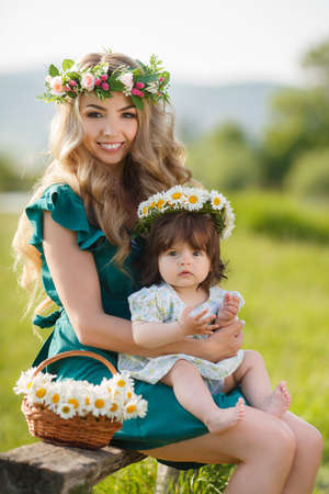 Young beautiful mother modelblonde with lush long hairbeautiful makeupon her head a wreath of flowers plays on a green meadow in summer with a young daughtera girl with brown eyes and luxuriant hairSunny day
