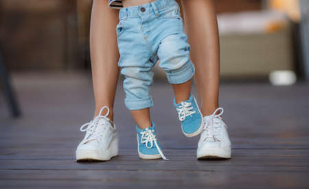 The first steps of the kid, Mom in white sneakers with a young son, dressed in blue pants and blue shoes, a warm summer day and learn to walk in the street, the first steps, the mother maintains her son.の写真素材