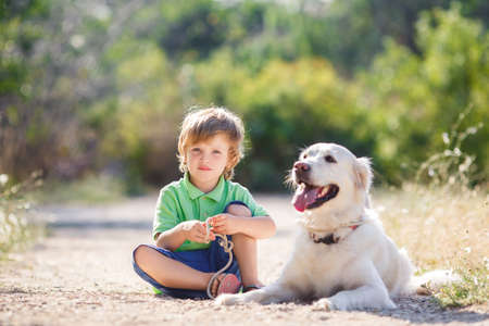 Little boy with a golden retriever dogs outdoor. Boy with a dog on the nature. child with dog outdoor. child and animal