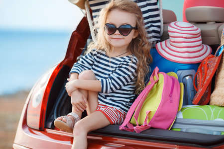 A little girl, a brunette with long curly hair, dressed in a striped sailor shirt, dark sun glasses, and a journey to the sea, sits in the trunk of the red car with clothes, suitcases and bags