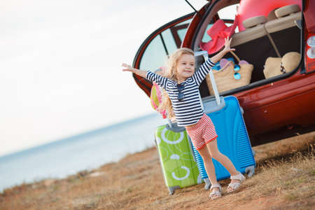 The little girl is going on a journey. A little girl, a brunette with long curly hair, dressed in a striped sailor shirt and shorts with red stripes, in dark sun glasses, embarks on a journey to the sea, stands near the red car loaded things, suitcases an