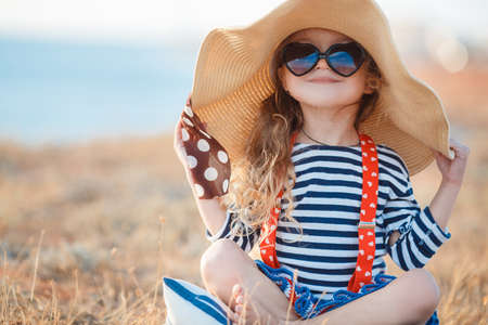 Happy little girl in a large hat, Beautiful young lady, a brunette with long curly hair, dressed in a striped sailor shirt and red suspenders, wearing dark sunglasses, sitting on a rocky beach in a big straw hat.