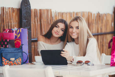 Two young beautiful women, good friends, a blonde and a brunette, with long straight hair, dressed in knitted light sweater, sitting at a table in a cafe, looking at pictures on digital tablet and drinking coffee in the fresh autumn air.