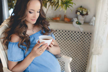 A young pregnant woman with a cup of tea.Beautiful young pregnant woman, brunette with long curly hair and light makeup, sitting on the floor at home with a cup of hot tea in his handsの写真素材