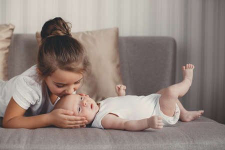 Photo pour A little girl five years old, a brunette, dressed in a white shirt and white pants, spends time together with her newborn brother, three-month-old boy, dressed in a white t-shirt and white panties, at home in the bedroom - image libre de droit