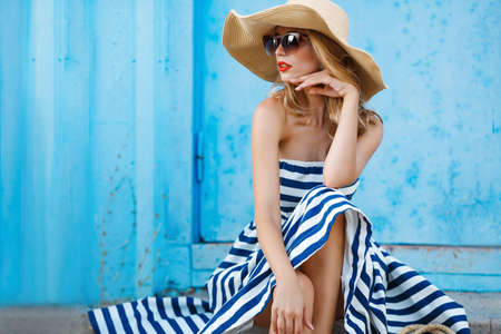 Foto de Woman portrait on blue background, sitting on the steps in a nice big straw hat and sun glasses, red lipstick and beautiful white teeth, with long blonde hair in a long striped dress with bare shoulders portrait of a model in the resort - Imagen libre de derechos