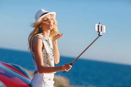 Photo pour Beautiful, slender woman, with long blonde hair, dressed in a white jumpsuit and a white hat outdoors in summer time, near the red car taking pictures of himself using a smartphone and selfie stick in the background the rocky shore of the ocean - image libre de droit
