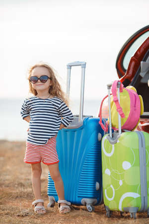 Beautiful little girl, brunette with long curly hair, dressed in a striped t-shirt and shorts with red stripes, with dark glasses from the sun, goes on a journey to the sea, stands near a red car loaded with suitcases and bags