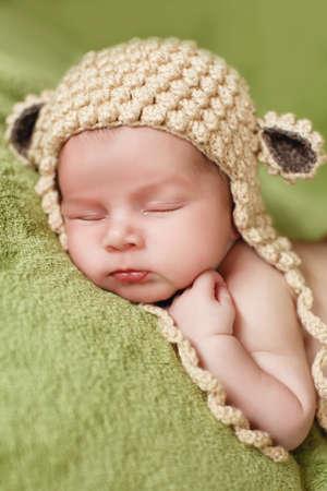 Peaceful sleep of a newborn baby. Newborn baby in brown knitted hat sleeping sweetly on a soft green blanket handles himself under his cheek