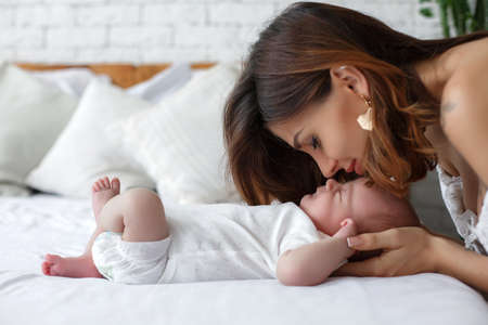 Photo pour Happy mother in bed with her baby. Portrait of a beautiful loving mother playing first games with her baby in the bedroom. Mother is feeling love and smiling to her kid. Love and relation bond of mother and child concept. - image libre de droit