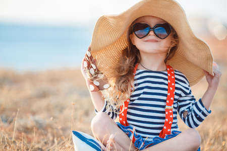 Foto de Happy little girl with long blond hair in a straw hat and sunglasses walks on a meadow at sunset with a seascape on the background. Ð¡hild plays alone in nature while sitting on dry grass near a pond. - Imagen libre de derechos