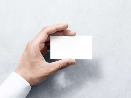 Foto de Hand hold blank plain white business card design mockup. Clear calling card mock up template holding arm. Visit pasteboard paper surface display front. Check small offset card print. Business branding - Imagen libre de derechos