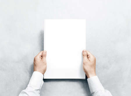 Foto de Hand holding white journal with blank cover mockup. Arm in shirt hold clear magazine template mock up. A4 book softcover surface design. Paperback print display show. Closed notebook cover showing. - Imagen libre de derechos