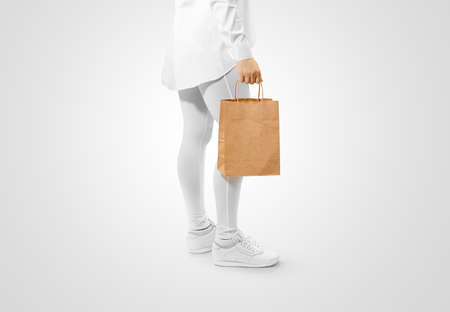 Photo pour Blank brown craft paper bag design mockup holding hand, clipping path. Woman hold kraft textured purchase pack mock up. Clear shop bagful branding template. Shopping carry package in persons arm. - image libre de droit