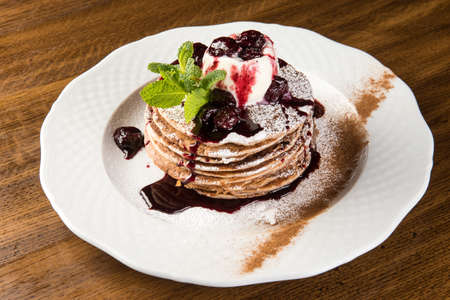 Chocolate Pancakes with Vanilla Ice Cream and Warm Cherry Sauce on white plate