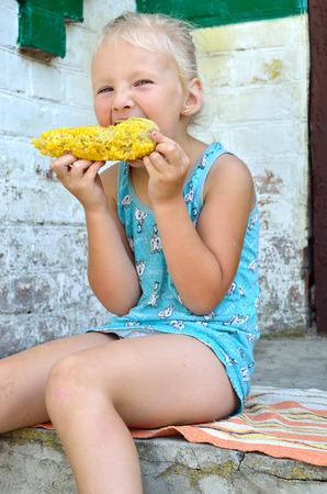 Foto für Little girl smiles and eats boiled corn - Lizenzfreies Bild