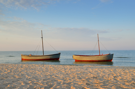 Photo pour Fishing boats moored near the shore at sunset background - image libre de droit